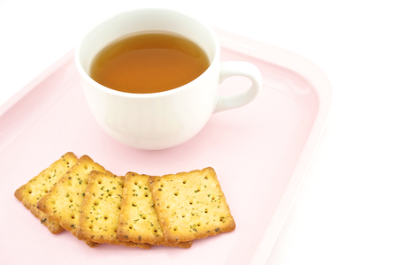 Tea in white cup and biscuits at side put on pink tray isolated on white  photo