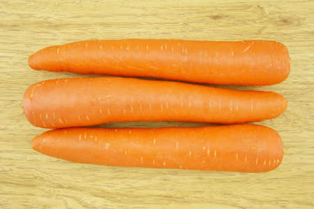 carotene: Carrot is orange vegetable with carotene put on wood background.