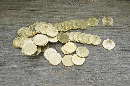 disperse: Gold coin of Thai baht disperse on black wood background.