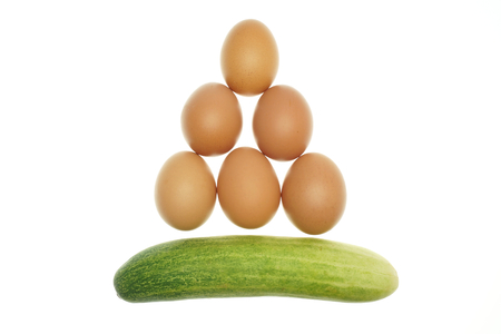 Egg put as triangle and cucumber isolated with white background. photo