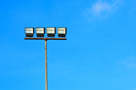 Spotlight halogen for irradiate to the football field with blue sky background.