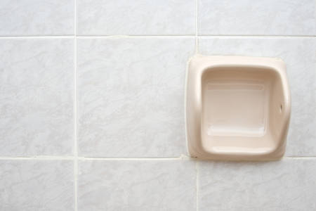 empty cream tissue holder on right of the bathroom wall. stock