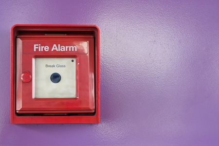 Red box of fire alarm with black button on violet background  photo