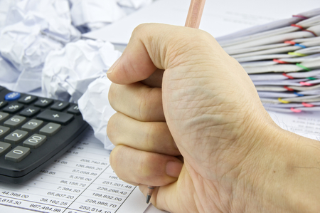 Man angry hold pencil with pile of paperwork as background. photo