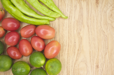 vegetate: Fresh green goat pepper with tomato and lemon on side of wood background. Stock Photo
