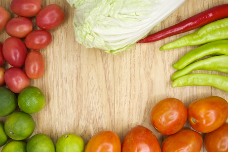 Fresh red and green goat pepper with tomato and lettuce on wood background. photo