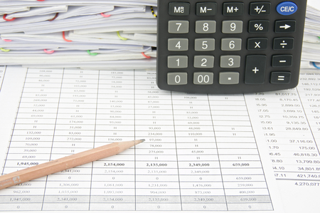 workload: Brown pencil and vertical calculator place on finance account with pile of paperwork as background. Stock Photo