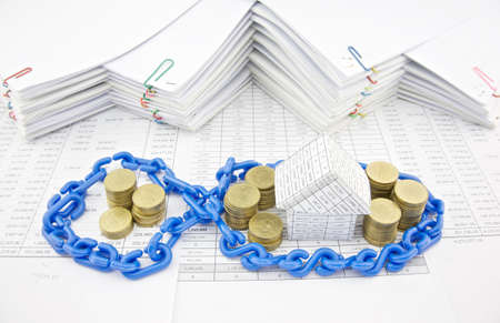 workload: House and pile of gold coins in blue plastic chain on finance account with pile of paperwork as background.