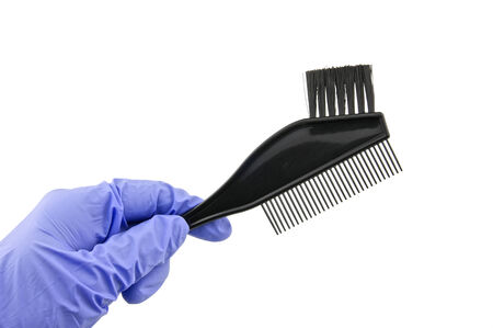 latex glove: Man wear purple latex glove holding back brush for hair dye isolated with white background.
