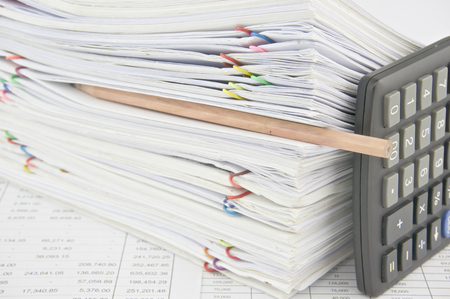 workload: Brown pencil put in stack paperwork with vertical calculator on finance account with pile of paperwork as background. Stock Photo