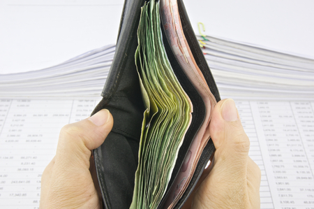 Man open wallet full of bills with pile of paperwork as background. photo