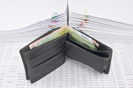workload: Wallet full of bills with pile of paperwork as background.