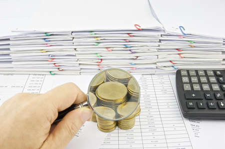 workload: Man hold magnifying glass on stack of gold coins with pile of paperwork as background.