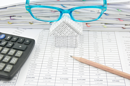 Brown pencil and blue glasses on house with calculator on finance account with pile of paperwork as background. photo