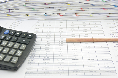 workload: Bottom of brown pencil and calculator on finance account with pile of paperwork as background. Stock Photo