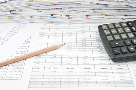 balance: Brown pencil and calculator on finance account with pile of paperwork as background. Stock Photo