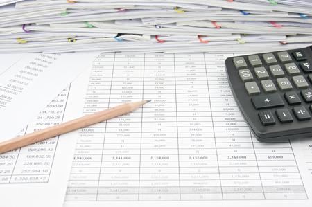 balanza: L�piz Brown y calculadora en las finanzas representan con la pila de papeleo como fondo. Foto de archivo