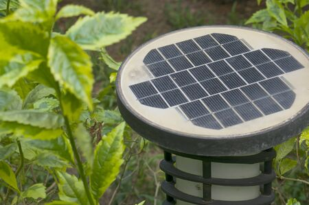 powered: Old black and white solar powered with lanterns in garden.