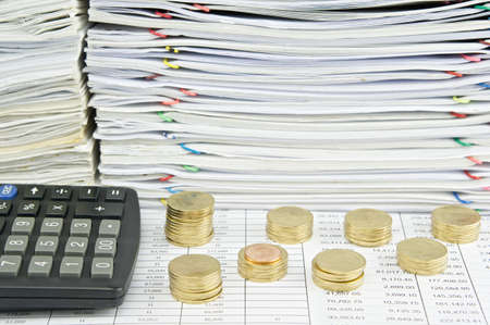 workload: Pile of gold coins with calculator and pile of paperwork as background. Stock Photo