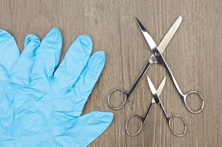 latex glove: Big and small silver surgical scissors place beside blue latex glove on wood background.