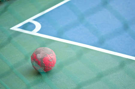 Old red ball at corner in green and blue futsal field. photo