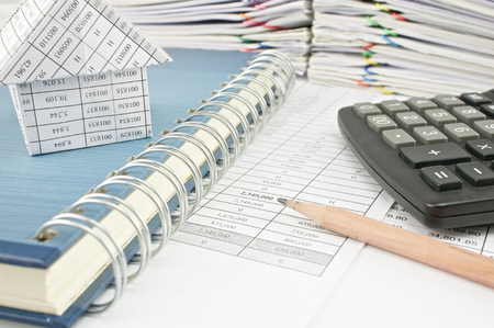 Close up pencil and house on notebook with calculator on finance report with pile of paperwork as background.