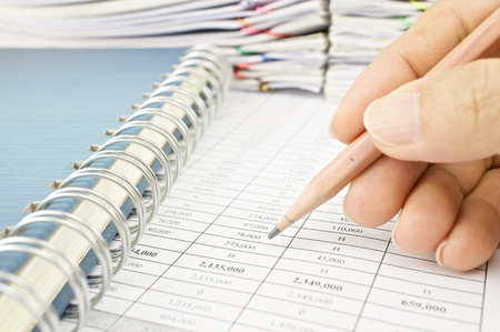 Man is auditing account by pencil with notebook and pile of paperwork as background. photo