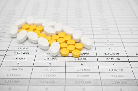 painkiller: Pile of white and yellow pills for painkiller on finance report.
