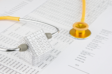 pinch: Yellow and gold stethoscope pinch house place on finance account.