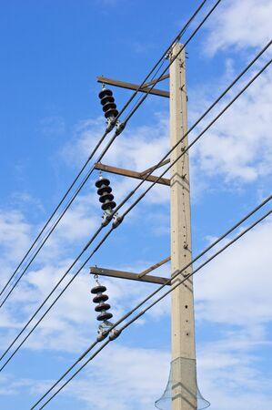 watts: High electricity post and cable line with blue sky as background.