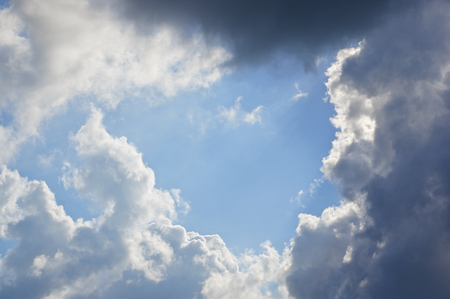nebulosity: White cloud like baby crawl and raincloud on blue sky as a background. Stock Photo