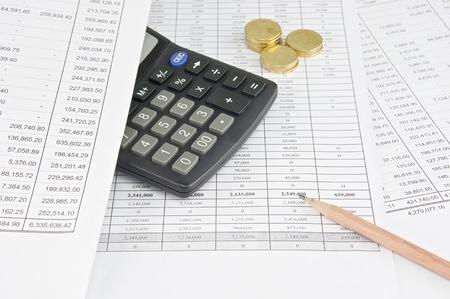 workload: Pencil with calculator and gold coin put on finance account. Stock Photo