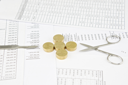 sheet pile: Scalpel and surgical scissors between pile of gold coins as plus on balance sheet. Stock Photo