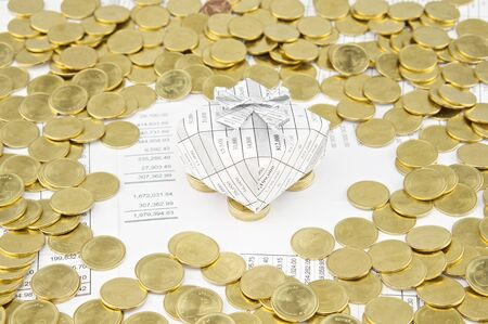 sheet pile: Gift box on pile of gold coins have gold coins around on balance sheet. Stock Photo