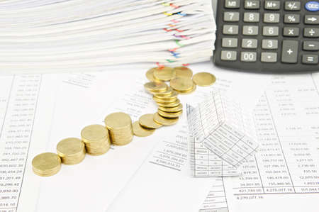 sheet pile: Bankruptcy of house and step pile of gold coins on balance sheet have calculator and pile of paperwork as background.