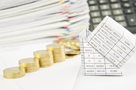 sheet pile: Close up bankruptcy of house and step pile of gold coins on balance sheet have calculator and pile of paperwork as background. Stock Photo