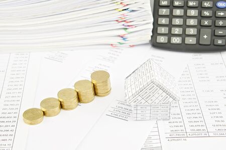 sheet pile: Step pile of gold coins and house on balance sheet have calculator and pile of paperwork as background. Stock Photo