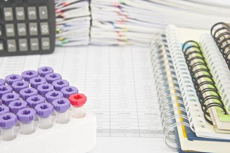 balanza de laboratorio: Tubos de vac�o Red de recogida de muestras de sangre y port�til con calculadora en cuenta las finanzas tienen pila de papeleo como fondo. Foto de archivo