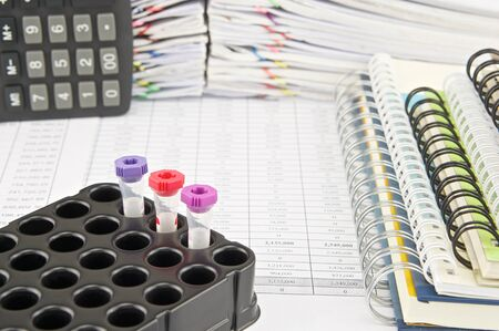 phlebotomy: Vacuum tubes for collecting blood samples and notebook with calculator on finance account have pile of paperwork as background. Stock Photo