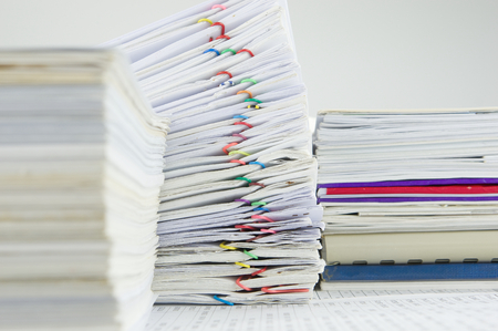 Colorful paper clip on pile of report have blur pile of paperwork as foreground and background.