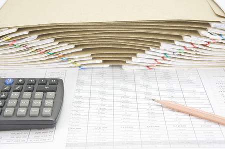 calculator: Brown pencil with calculator on finance account have brown envelope between overload of old paperwork as background.