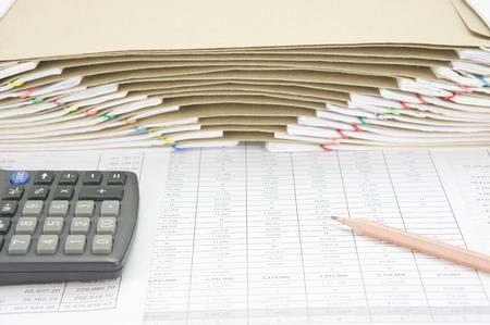 calculadora: l�piz de color marr�n con la calculadora en cuenta las finanzas tienen sobre marr�n entre sobrecarga del papeleo vieja como fondo. Foto de archivo