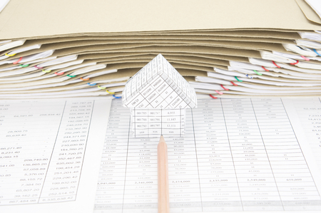 workload: Brown pencil point to house on finance account have brown envelope between overload of old paperwork as background. Stock Photo