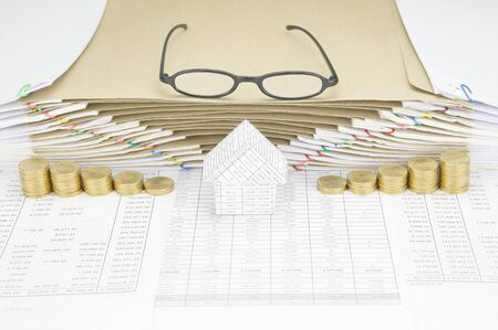 old envelope: House between step of gold coins on finance account have spectacles on top of brown envelope between overload of old paperwork as background. Stock Photo