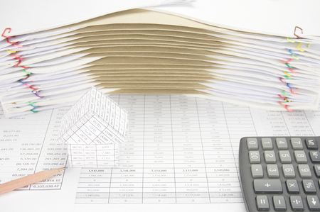 old envelope: House and pencil with calculator on finance account have brown envelope between overload of old paperwork as background.