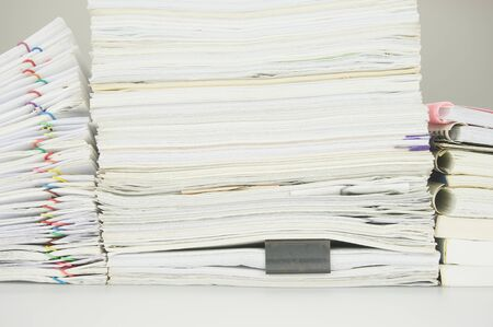 workload: Paper of report and paperwork with books on table near wall. Stock Photo