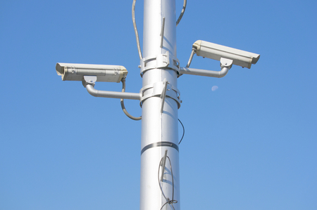 Security camera on high pole at super highway with blue sky.