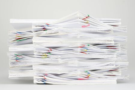 white sheet: Overload document of report and receipt with colorful paperclip on white table. Stock Photo