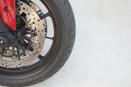 alloy wheel: Black magnesium alloy wheel of red motorcycle and disc brake on the left.