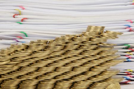 derrumbe: Paso pila de monedas de oro colapso con la pila de papeles como fondo.